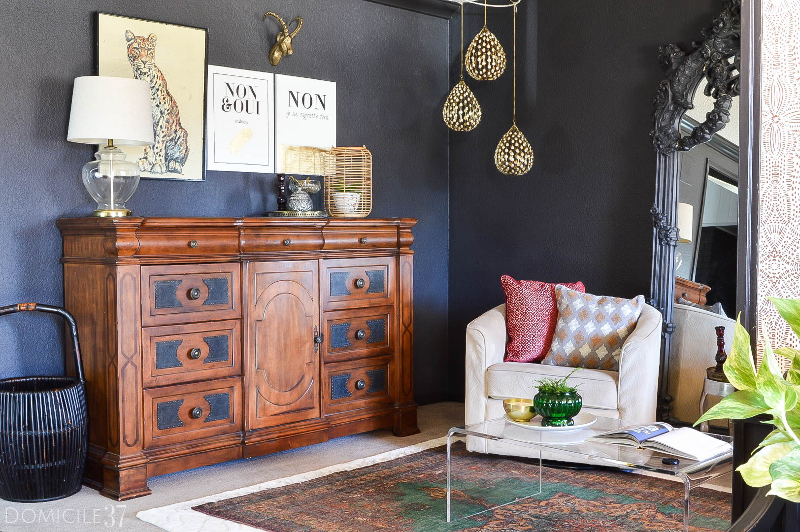 Vintage Eclectic Sitting room inspired by Moroccan decor | Layered persian rugs | Dresser console on black wall with chic art | vintage art | acrylic coffee table with swivel chairs