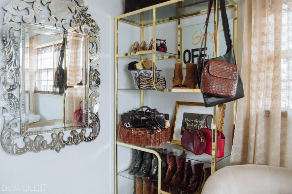 Clothes and shoes stored on vintage brass and glass shelves