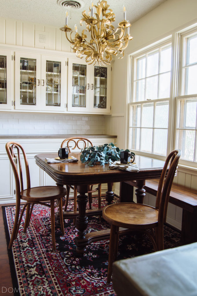 Cottage style kitchen with gold Italian Tole Chandelier and vintage wooden table and bentwood cane chairs