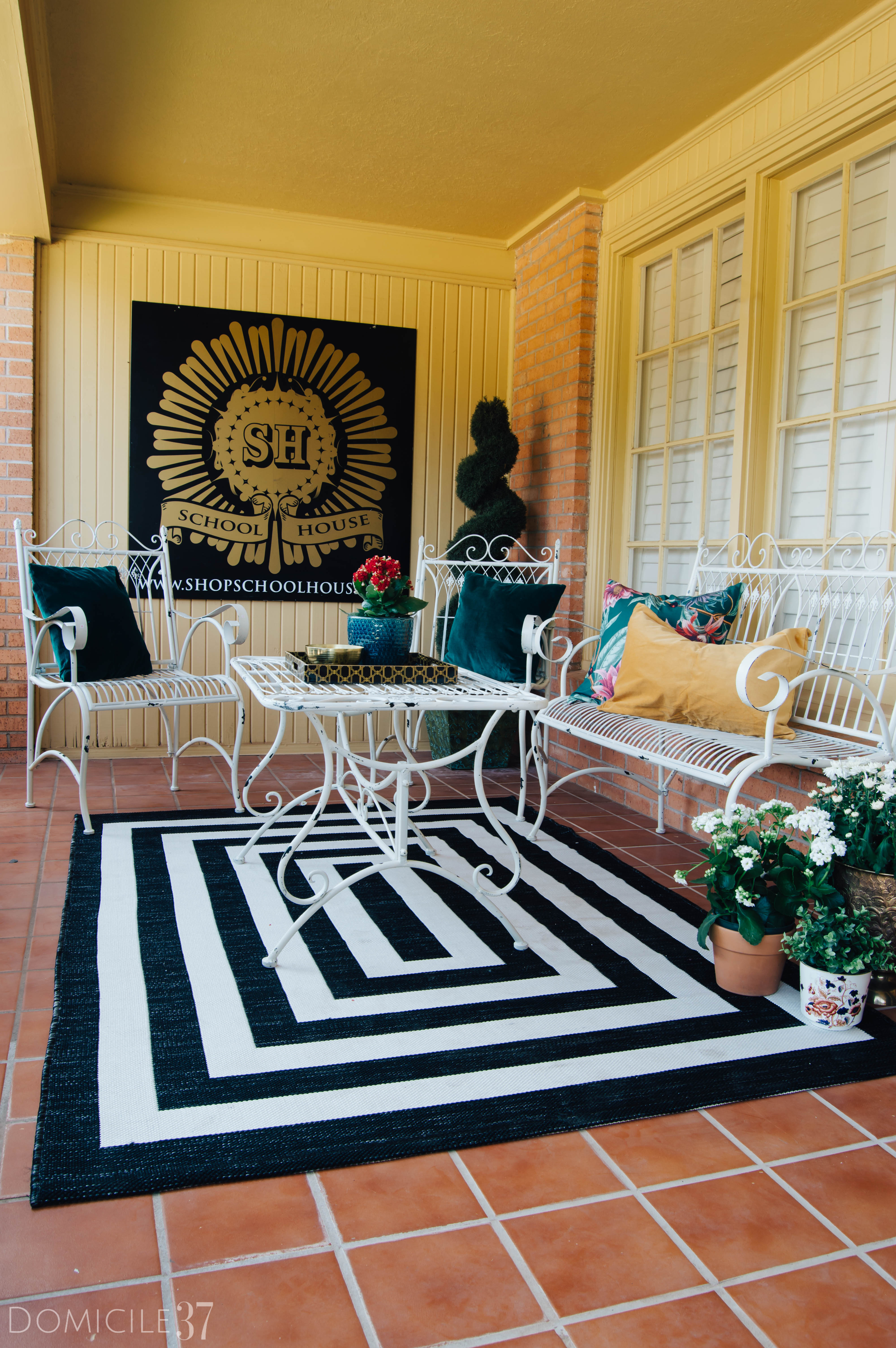 Terracotta porch with wrought iron furniture, metal outdoor wall decor, color outdoor pillows, black and white rug