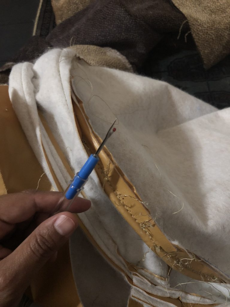 Using seam ripper to remove thread from vinyl fabric