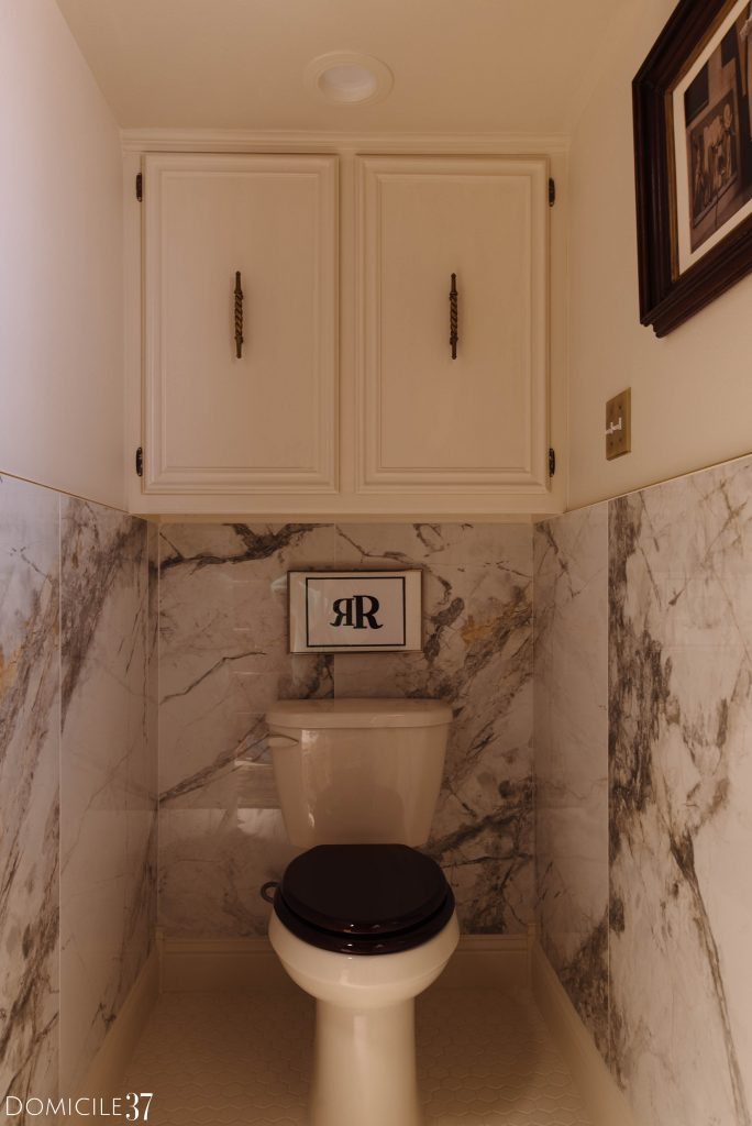 bathroom toilet area with porcelain tile wall