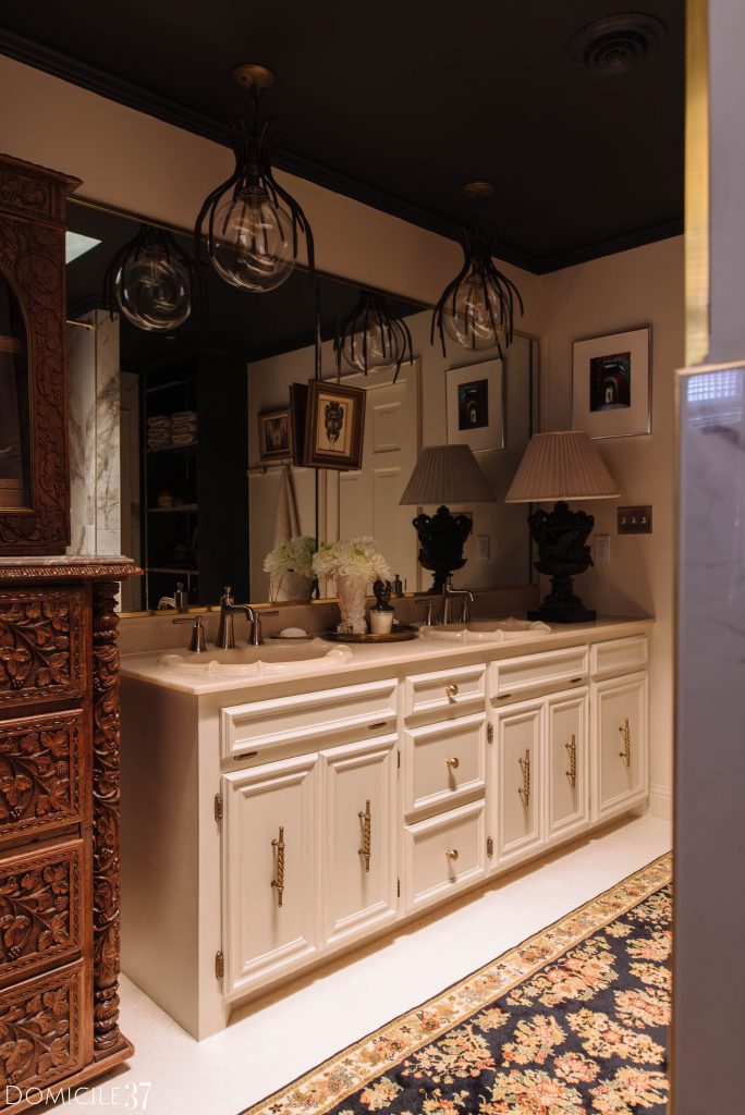 Bathroom vanity with antique brass hardware and vintage light fixtures